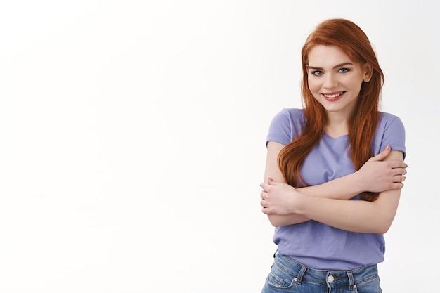 Koud worden, vrouw wil knuffelen of iets warms kopen, koop online. aantrekkelijke aangenaam lachende roodharige vrouw in t-shirt, eigen lichaam omarmen, armen over de borst gekruist, staande witte muur