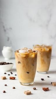 Koud zet koffie met kruiden en melk op lichtgrijze oppervlakte