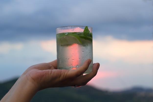 Koud zomerdrankje met limoen en munt op een balkon