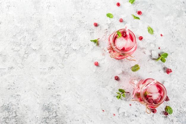 Koud zomers drankje, frambozensangria, limonade of mojito met verse frambozen en siroop, muntblaadjes, op grijze steen copyspace bovenaanzicht