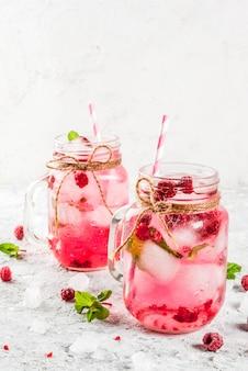 Koud zomers drankje, frambozensangria, limonade of mojito met verse frambozen en siroop, muntblaadjes, op grijze steen copyspace