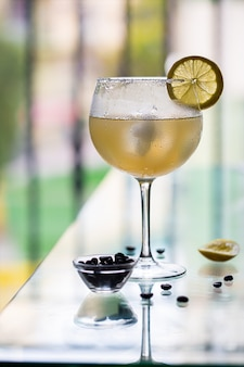 Koude alcoholische cocktail cuba libre in een beslagen glas met citroen en koffiebonen