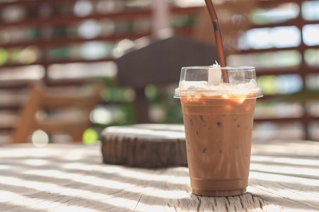 Koude cacao in een plastic mok die op een houten lijst wordt geplaatst