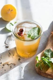 Koude citroen groene thee in glas met anijsijs. heide probiotisch drankje in de zomer