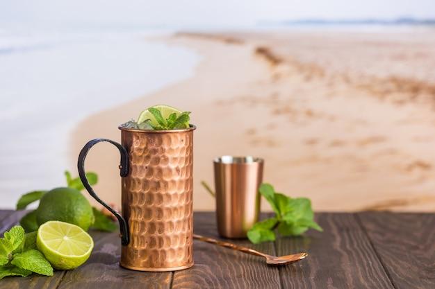 Koude cocktail van moskou-muilezels met gemberbier, wodka en limoen op het strand en aan zee