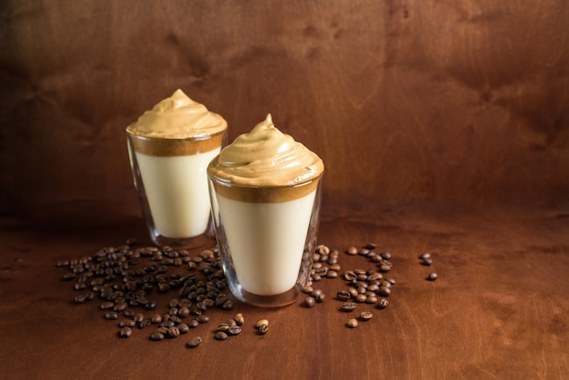 Koude dalgona koffie in heldere glazen op een donkere houten achtergrond