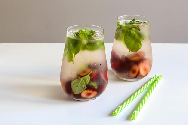 Koude dranken in klein glaasje kersen en muntlimonade mojito cocktail