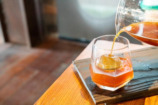 Koude druppel zwarte koffiepot met glas en ijs in coffeeshop café en restaurant
