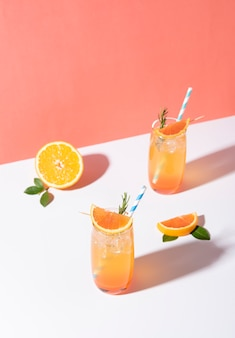 Koude en verfrissende sinaasappelpunchcocktail met sinaasappelschijfje op gele achtergrond. zomer drankje.