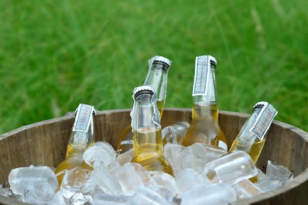Koude flessen bier in houten emmer met ijs