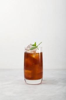 Koude fruitthee met ijs in een hoog glas