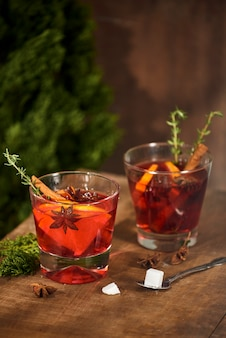 Koude gemberthee met sinaasappel en citroen in glazen bekers. thee met suiker. de inrichting. kaneel en rozemarijn kruiden