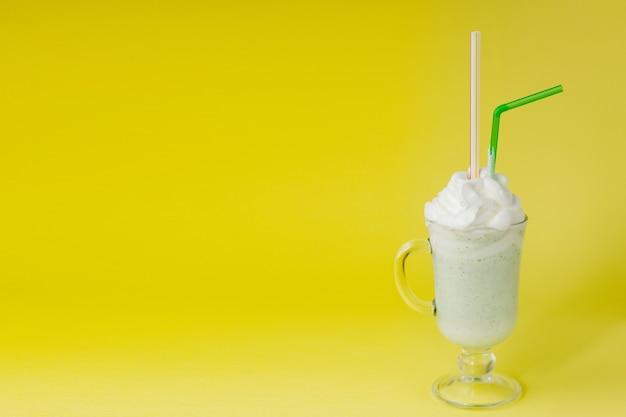 Koude groene pepermuntmilkshake op een gele achtergrond.