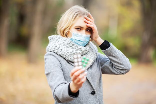 Koude herfst. vrouw die gezichtsmasker draagt en pillen onder bloeiende bomen in park houdt