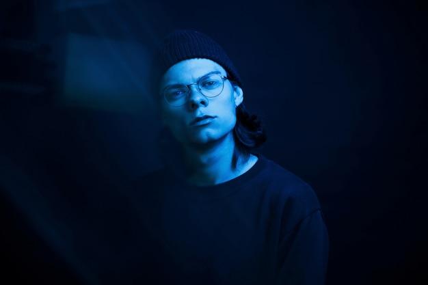 Koude kleur. studio opname in donkere studio met neonlicht. portret van ernstige man