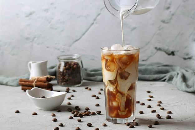 Koude koffie in een hoog glas met room die erin wordt gegoten en de textuur van de drank laat zien