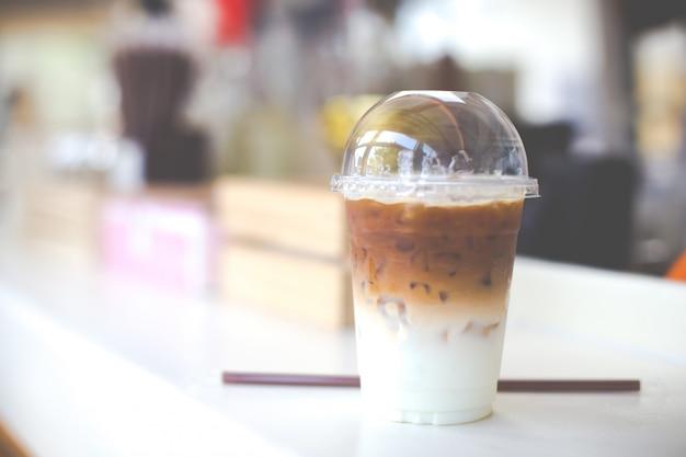 Koude koffie in plastic beker op een houten tafel in café