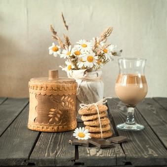 Koude koffie met melk en chocolade met koekjes en een boeket madeliefjes