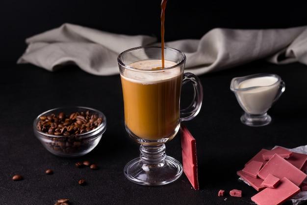 Koude koffie met melk en karamelsiroop op een zwarte achtergrond