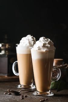 Koude koffiedrank frappe of frappuccino, met slagroom en chocoladeschilfers, met rietjes over donkere ondergrond