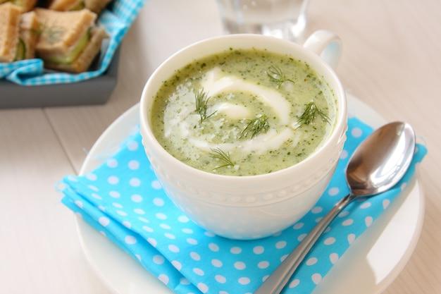 Koude komkommersoep met dille, yoghurt en broodjes op een dienblad