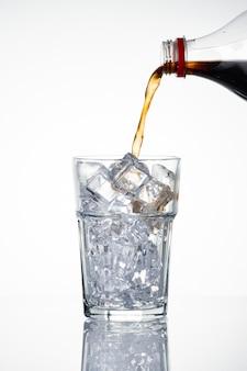 Koude koolzuurhoudende drank wordt over ijsblokjes in een glas gegoten