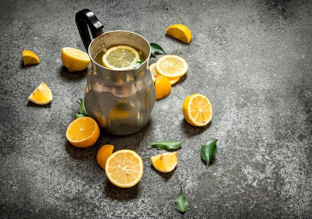 Koude limonade in een kan met schijfjes citroen en groene bladeren.