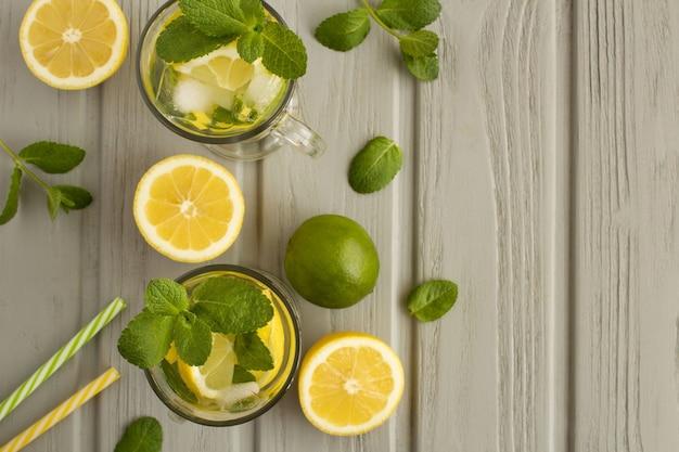 Koude limonade met citroen en munt in de glazen op de grijze houten achtergrond. bovenaanzicht. kopieer ruimte.