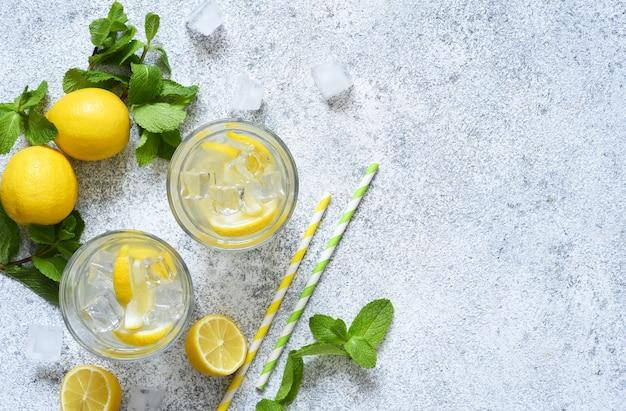Koude limonade met citroen, munt en ijs op een betonnen ondergrond.