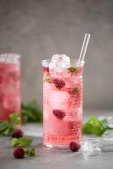 Koude limonade met verse frambozen en munt in hoge glazen