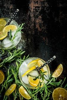 Koude limonade of alcohol wodka cocktail met citroen en rozemarijn, op een zwarte roestige metalen,
