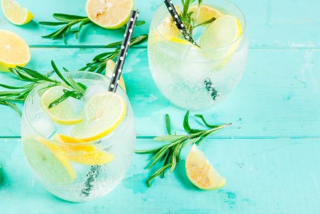 Koude limonade of alcohol wodka cocktail met citroen en rozemarijn, op lichtblauwe tafel,