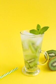 Koude limonade of doordrenkt water met kiwi in het glas op de gele achtergrond. locatie verticaal. kopieer ruimte.