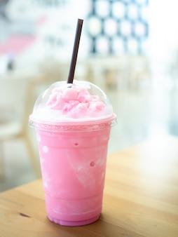 Koude melk smoothie in een plastic kop op een houten tafel