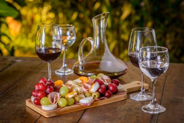 Koude schotel en wijnglazen op een houten tafel.