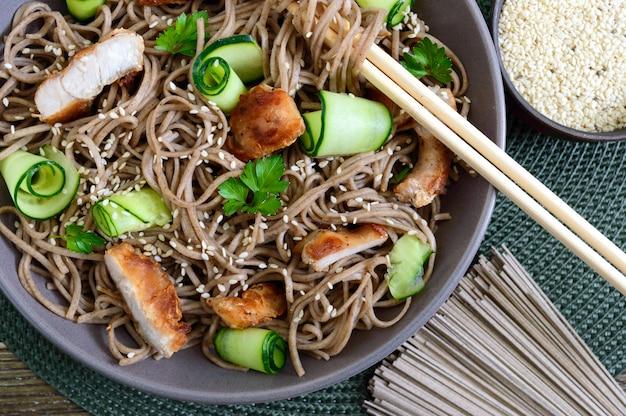 Koude soba met kip, verse komkommers, saus en sesam. klassieke koude salade met boekweitnoedels. japans eten. traditionele aziatische keuken. bovenaanzicht, plat lag. detailopname