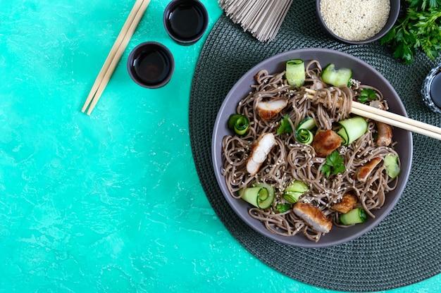 Koude soba met kip, verse komkommers, saus en sesam. klassieke koude salade met boekweitnoedels. japans eten. traditionele aziatische keuken. bovenaanzicht, plat lag.