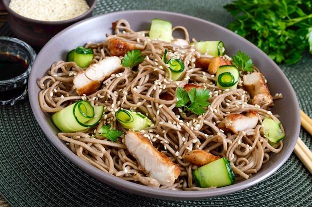 Koude soba met kip, verse komkommers, saus en sesam. klassieke koude salade met boekweitnoedels. japans eten. traditionele aziatische keuken. detailopname