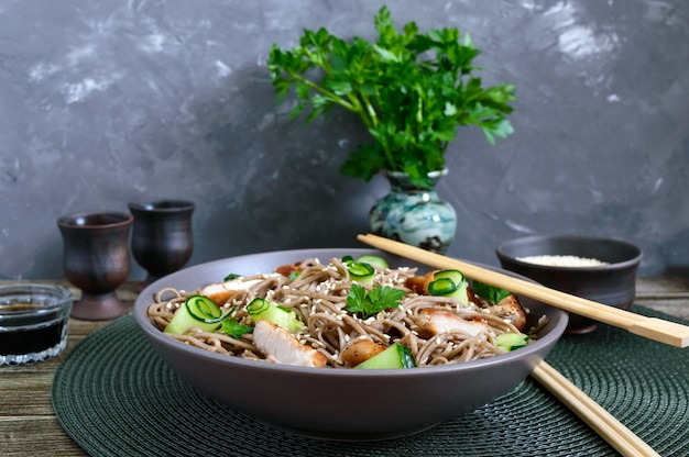 Koude soba met kip, verse komkommers, saus en sesam. klassieke koude salade met boekweitnoedels. japans eten. traditionele aziatische keuken.