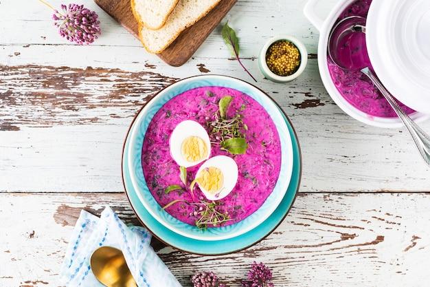 Koude soep gemaakt van bieten, komkommers en gegarneerd met een ei in een blauw bord op een houten ondergrond. bovenaanzicht.