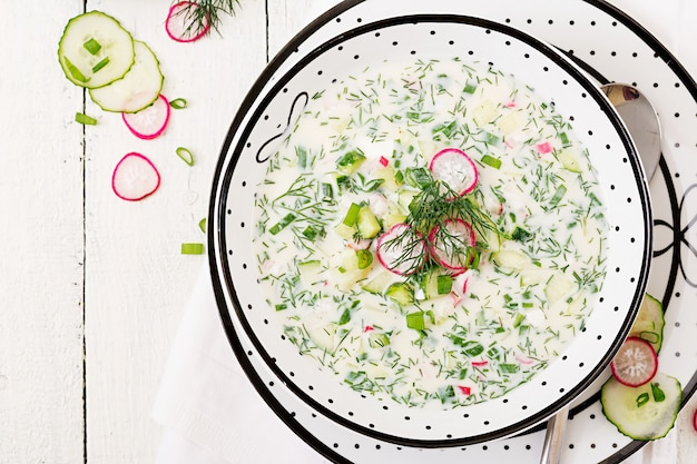 Koude soep met verse komkommers, radijs met yoghurt in kom op houten tafel. traditioneel russisch eten - okroshka. vegetarische maaltijd. bovenaanzicht plat leggen