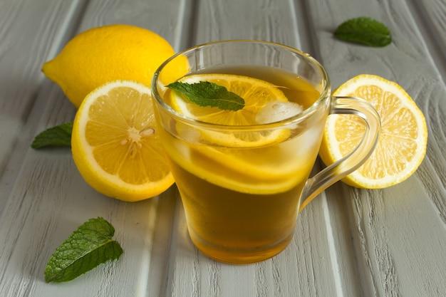 Koude thee met citroen in de glazen beker op de grijze houten achtergrond