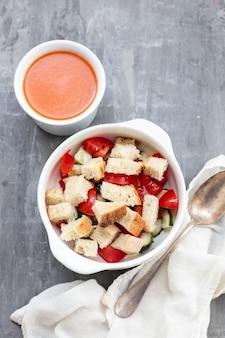 Koude tomatensoep gaspacho met brood in witte kom op keramische achtergrond