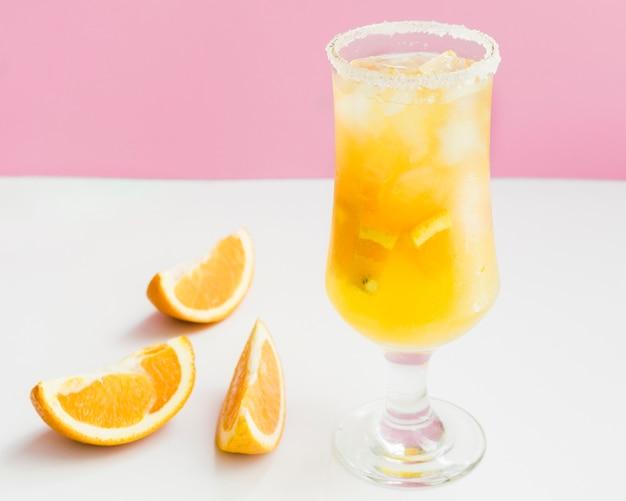 Koude tropische oranje cocktail met ijs, vers fruit