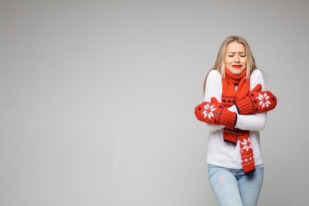 Koude vrouw in trui, sjaal en wanten die zichzelf omhelzen met gesloten ogen en een grimas waaruit blijkt dat ze koud en bevroren is. isoleer op grijs.