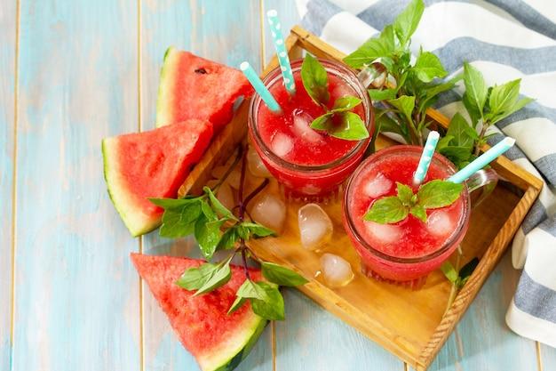 Koude watermeloen smoothie zomer watermeloen drankje in glazen en plakjes watermeloen