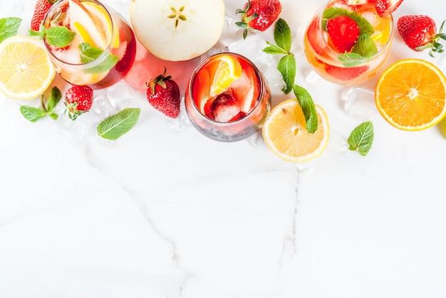Koude witte roze en rode sangria-cocktails met vers fruit bessen en mint.