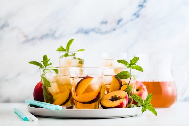Koude zomer thee met perzik en munt in glazen op tafel
