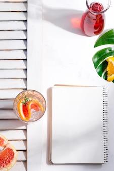 Koude zomer zelfgemaakte cocktail in een glas met schijfje grapefruit en notebook