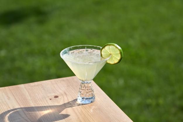 Koude zomerse heerlijke cocktails met limoen, munt en ijs in een glas met druppels. veelkleurige alcohol cocktaildrank aan de bar.
